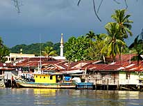 Miri/Sarawak/East-Malaysia (Borneo): Traditional stilt houses reflecting in the water of the Miri River